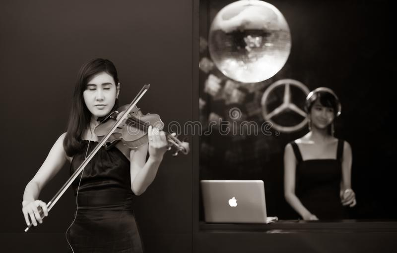 Blur Bangkok, Thailand  - April 06 2018 Unidentified model  Play music with violin and music from computer show in Bangkok. International Motor Show in Bangkok stock photo
