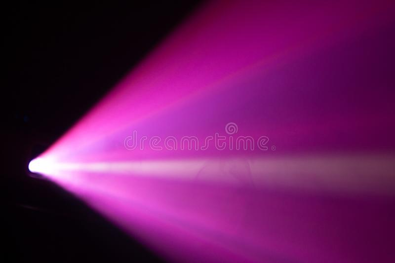 Blur beautiful pink color wide lens projector with light beam for movie and cinema at night . smoke texture spotlight . effects stock image