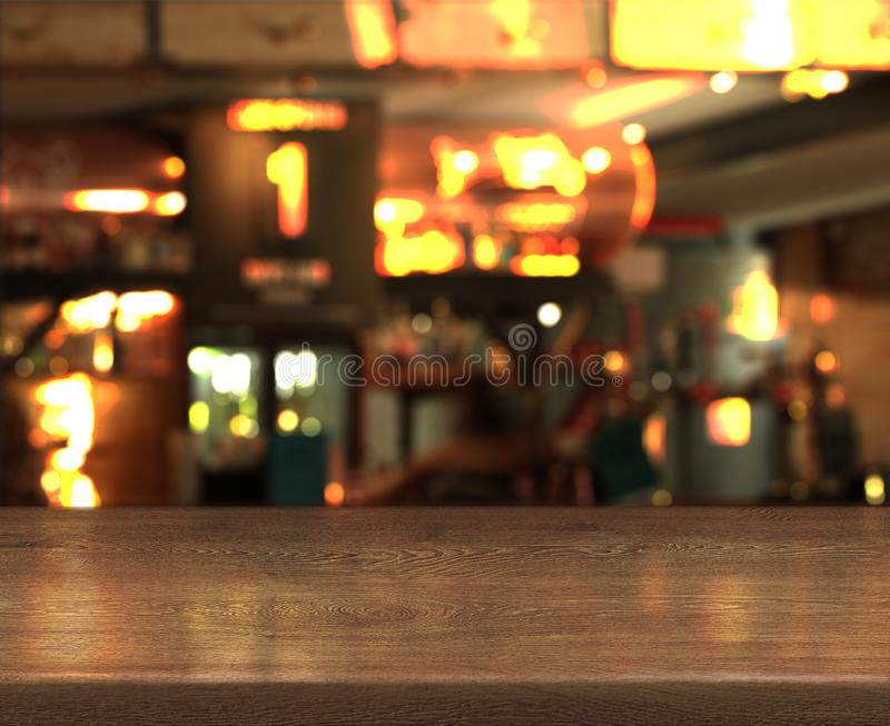 Blur bokeh background with empty wooden table top in night cafe. Blur bokeh background with empty wooden table top in night bar stock photo
