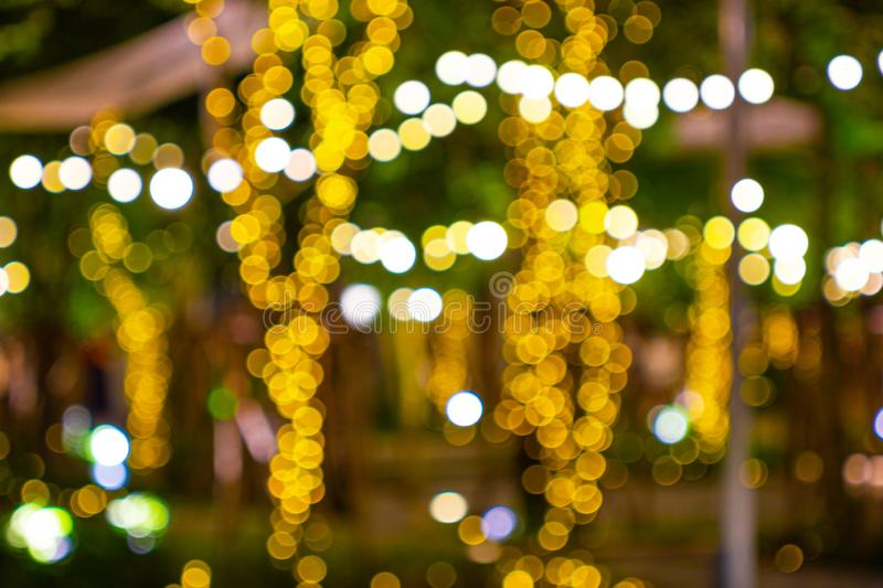 Blur - bokeh Decorative outdoor string lights hanging on tree in the garden at night time royalty free stock images
