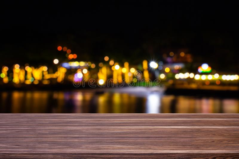 Blur cafe restaurant or resort close to the sea empty of dark wood table with blurred light gold bokeh abstract background for royalty free stock photography