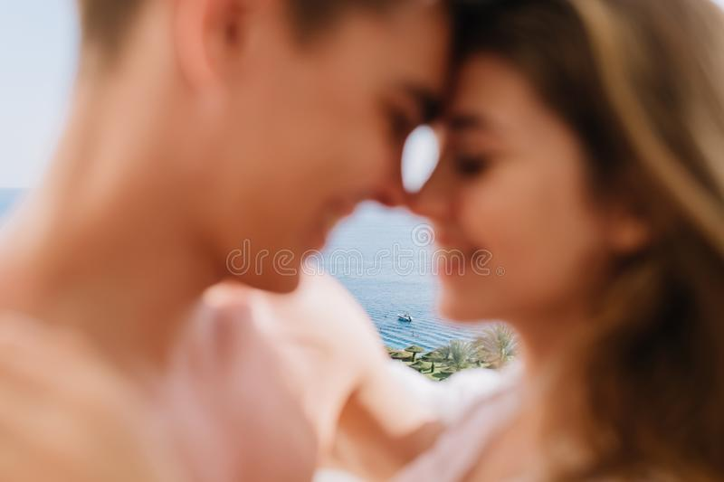 Blur close-up portrait of romantic young couple touching noses and cute smiling. Joyful laughing boy going to kiss his stock photography