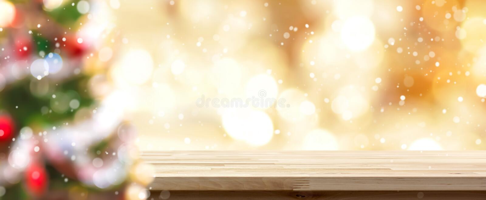 Blur colorful Christmas tree and gold bokeh with table top stock photo