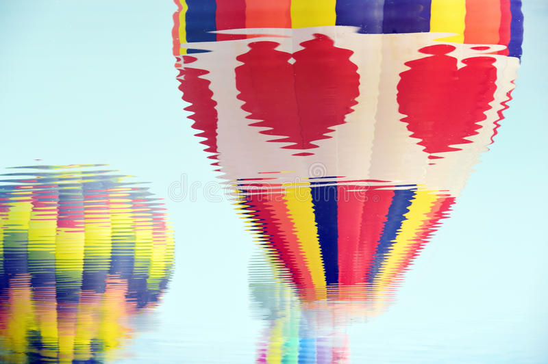 Blur of colorful hot air balloons against a blue sunset sky stock photography