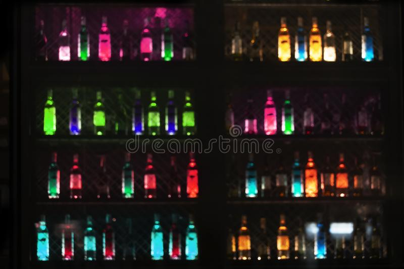 Blur glowing neon light of alcohol drinking bottle in bar or pub for dark night party background stock images