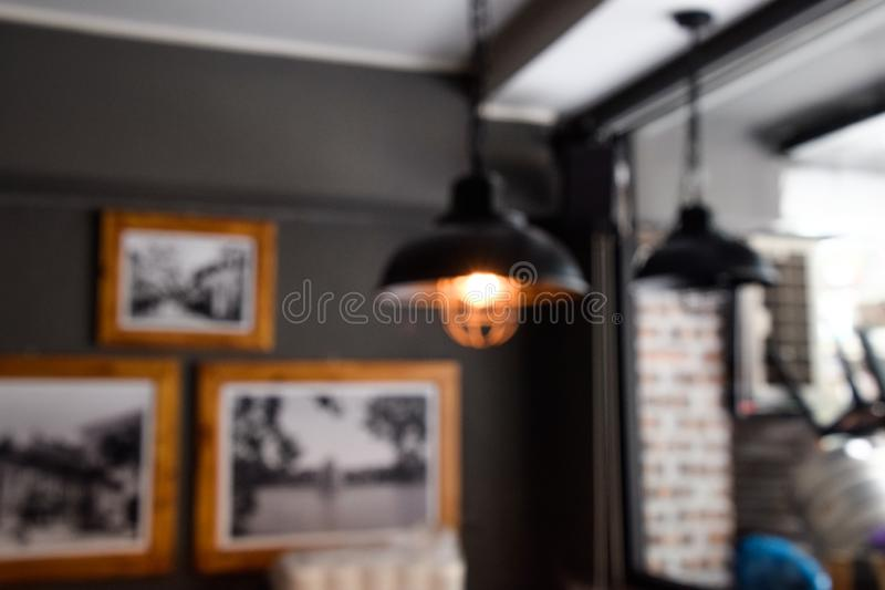 Blur image - Defocus or out of focus black lamp on the ceiling, sitting corner in the restaurant during the daytime - Blurred stock photo