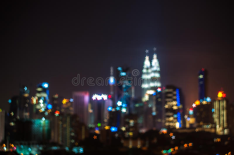 Blur image of Kuala Lumpur city, star bokeh shape. Bokeh has been defined as the way the lens renders out-of-focus points of light.Differences in lens royalty free stock photo