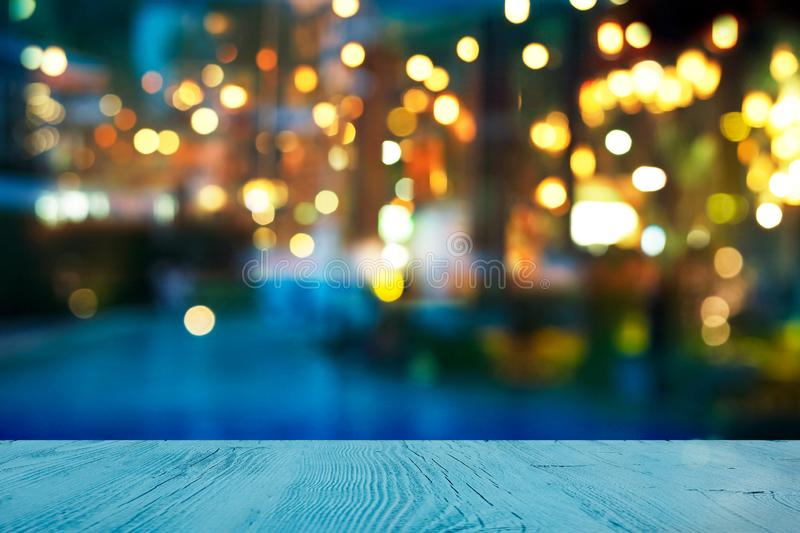 Blur light of bar or pub beside blue water swimming pool summer party at night with top of wood table background royalty free stock photo
