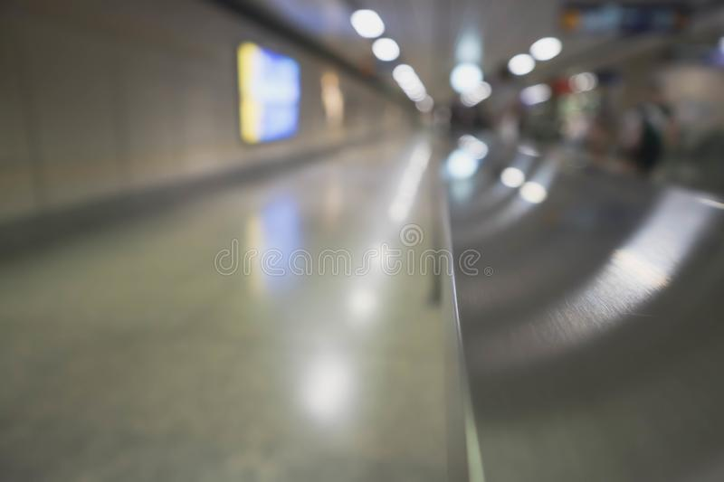 Blur photo of hand rail, walk way and background in subway. Daily life in public transportation. Copy space for text  and editing. Blur background photo stock photo