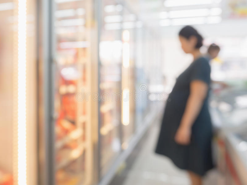 Blur pregnant woman at Frozen food section royalty free stock images