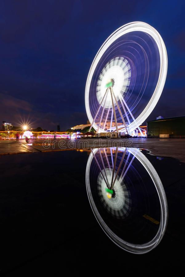 Blur rotate moving of Ferris wheel with lighting reflection on water. At carnival park in night time royalty free stock photo