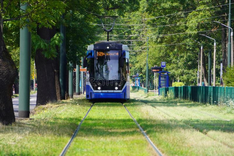 Blur, the tram goes on rails in the alley of trees. eco-friendly urban public transport. urban forestry, protection of the. Blur, the tram goes on rails in the royalty free stock photography