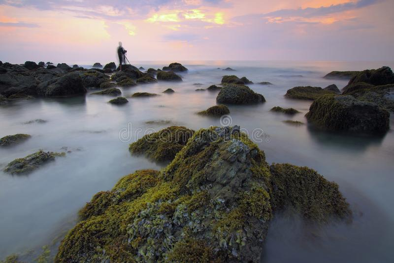 Blur of water on rocks at sunset royalty free stock photography