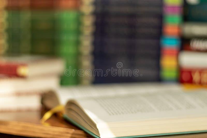 Blured开放书和堆各种各样的书在背景的许多书堆与copyspace 库存图片