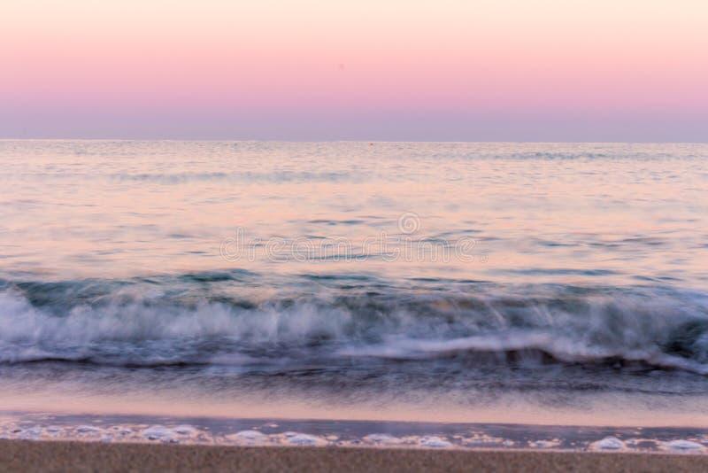 blured波浪 在海水反映的日出颜色 免版税库存图片
