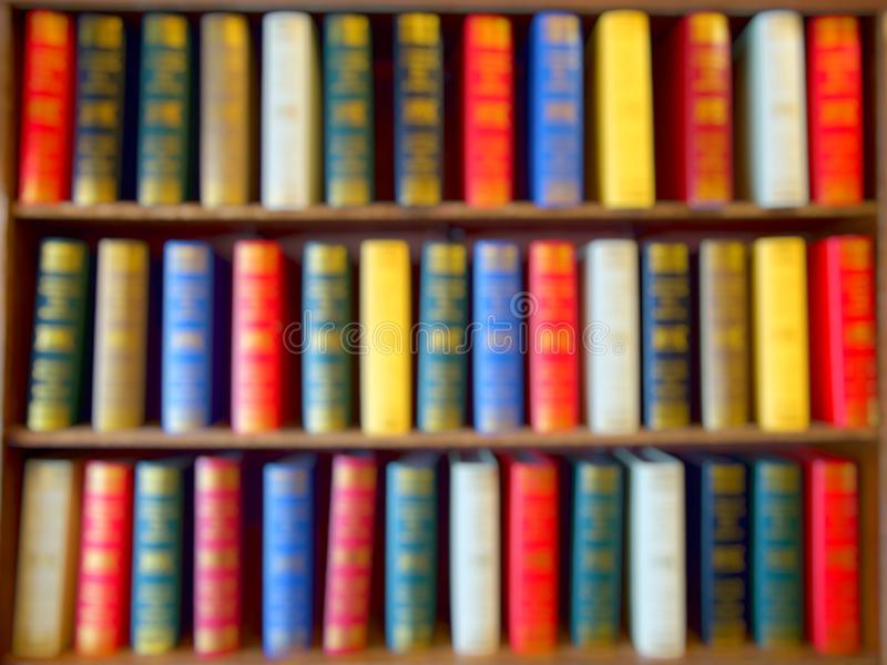 Blured των ζωηρόχρωμων βιβλίων, εγχειρίδιο, λογοτεχνία στο ξύλινο ράφι στη βιβλιοθήκη Υπόβαθρο στοκ εικόνες με δικαίωμα ελεύθερης χρήσης