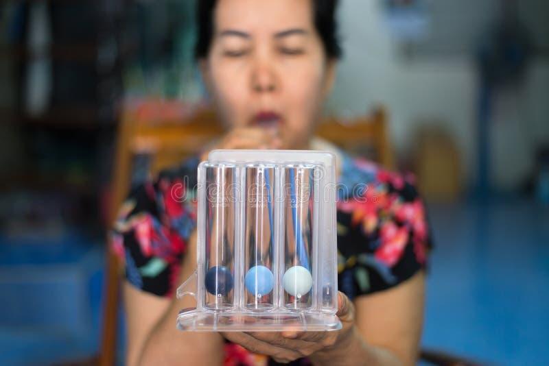 Blured av den tålmodiga användande incentivespirometeren eller tre bollar för stimulerar lungan arkivfoton