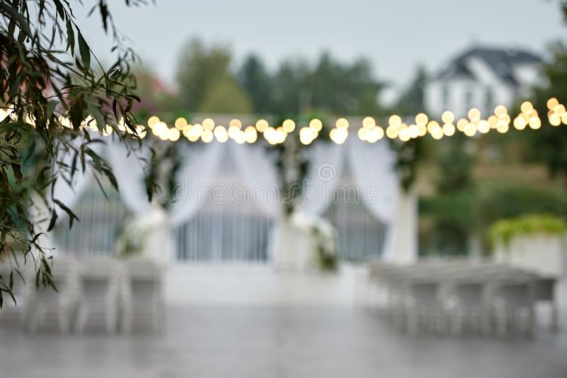 Blured background with wedding arch, chairs on each side of archway and bulb lights on wedding ceremony outdoors, copy space. Decor, decoration, flower royalty free stock photos