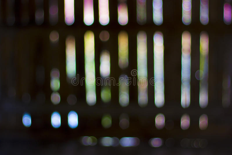 Blured bokeh lights in a row. Abstract defocused coloured background. Abstract background. Photo taken trough some holes in a wall. Blured bokeh defocused pastel royalty free stock images