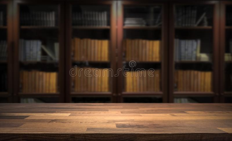 Blured bookshelf in small home library in the background. Table top for product display montage. Dark interior design royalty free stock photos