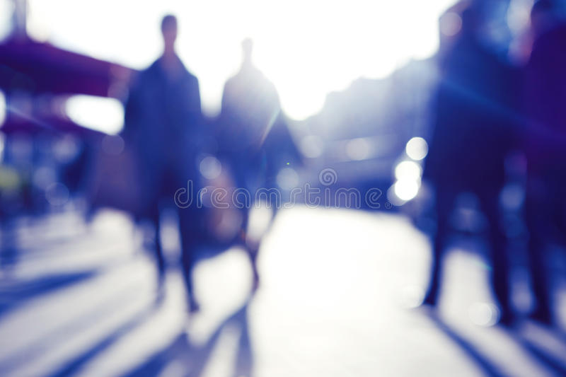 Blured image of people walking in the street. City commuters. High key blurred image of people walking in the street. Unrecognizable