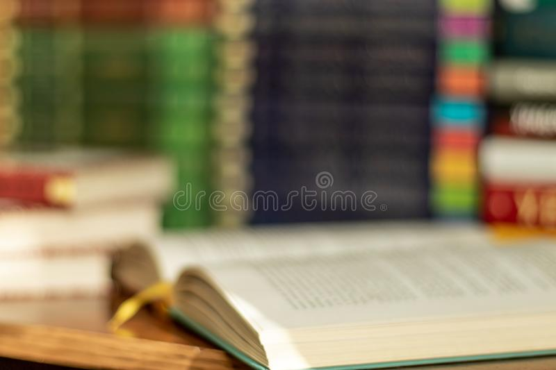 Blured open book and stacks of varied books many books piles on background with copyspace stock images