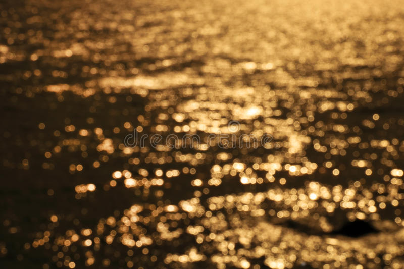 Blured surf sea wave at golden light sunset beach background stock photo
