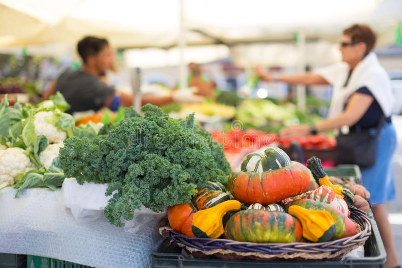 Blured unrecodnised people buying homegrown vegetable at farmers` market stall with variety of organic vegetable. Blured random unrecodnised people buying daily stock image