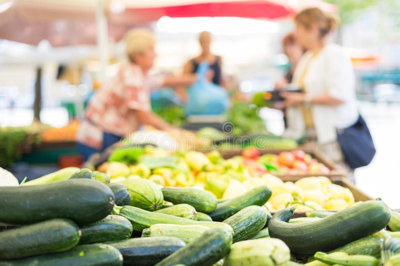 Blured unrecodnised people buying homegrown vegetable at farmers` market stall with variety of organic vegetable. Blured random unrecodnised people buying daily stock photos