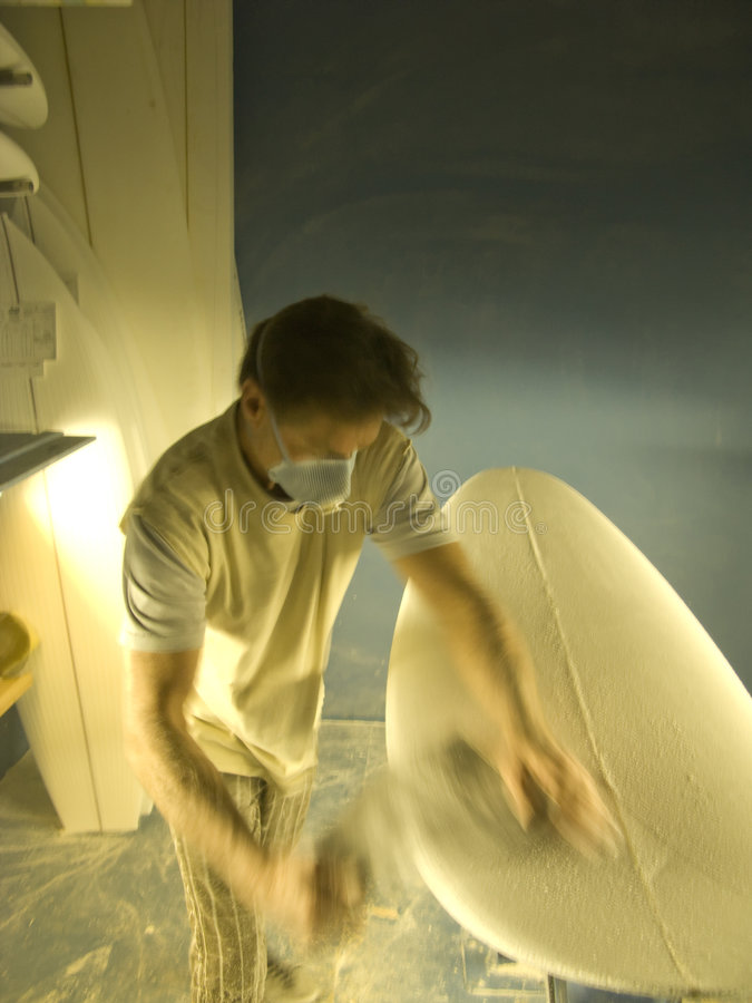 Blured view of a Man shaping a Surfboard stock photos