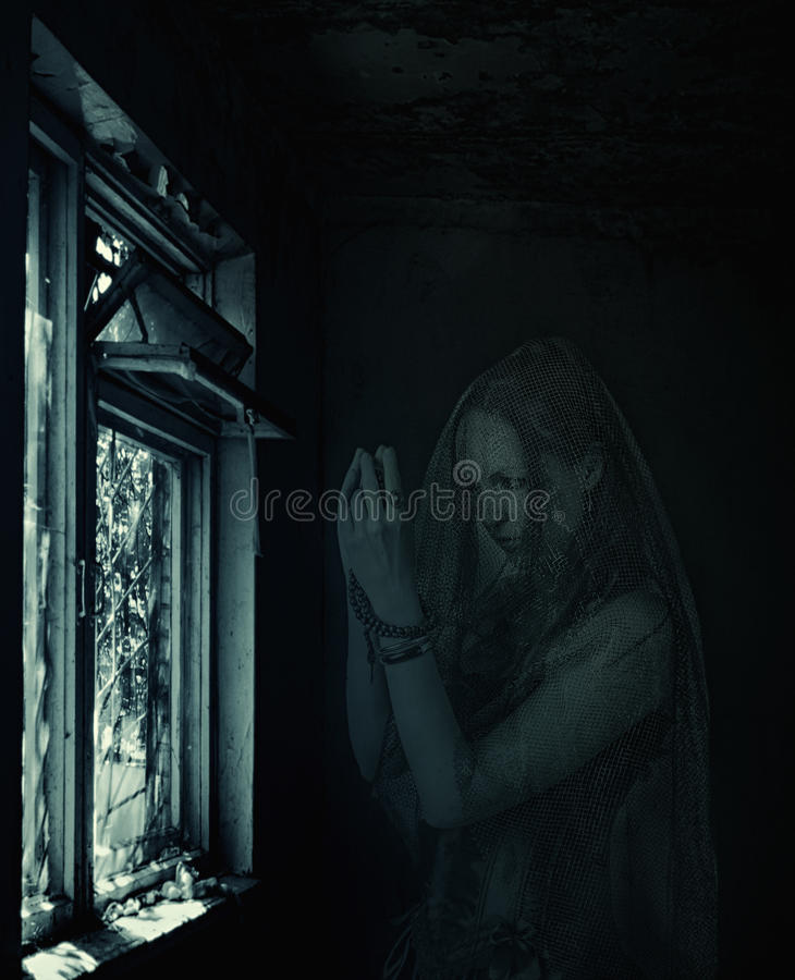 Blured woman ghost praying in old house. Halloween horror scene. Sad scary transparent blured woman ghost praying about window in old house stock image