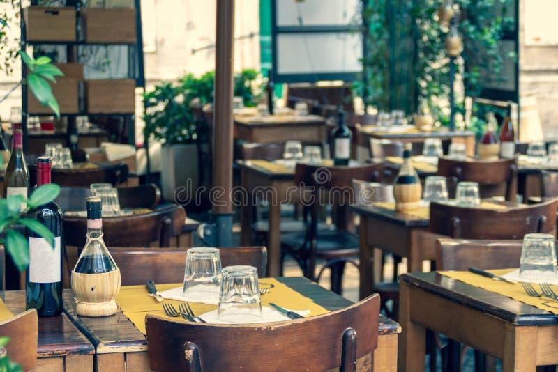 Bluredachtergrond van comfortabel Italiaans openluchtrestaurantterras met gediende houten lijsten en stoelen stock foto
