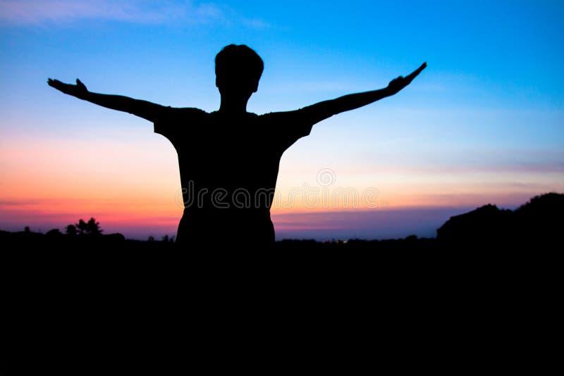 Blurr Силуэт, азиатский молодой человек в руке шляпы стоя открытой счастливой на горном пике над ligth захода солнца, стоковые изображения rf