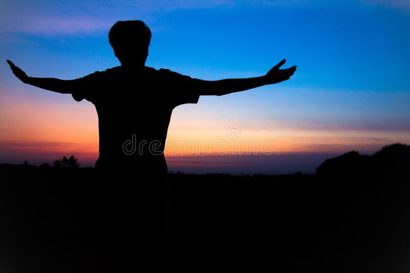 Blurr. Silhouette,Asian young man in hat hiking standing open arm happy at mountain peak above sunset ligth. Hiker outdoor stock image