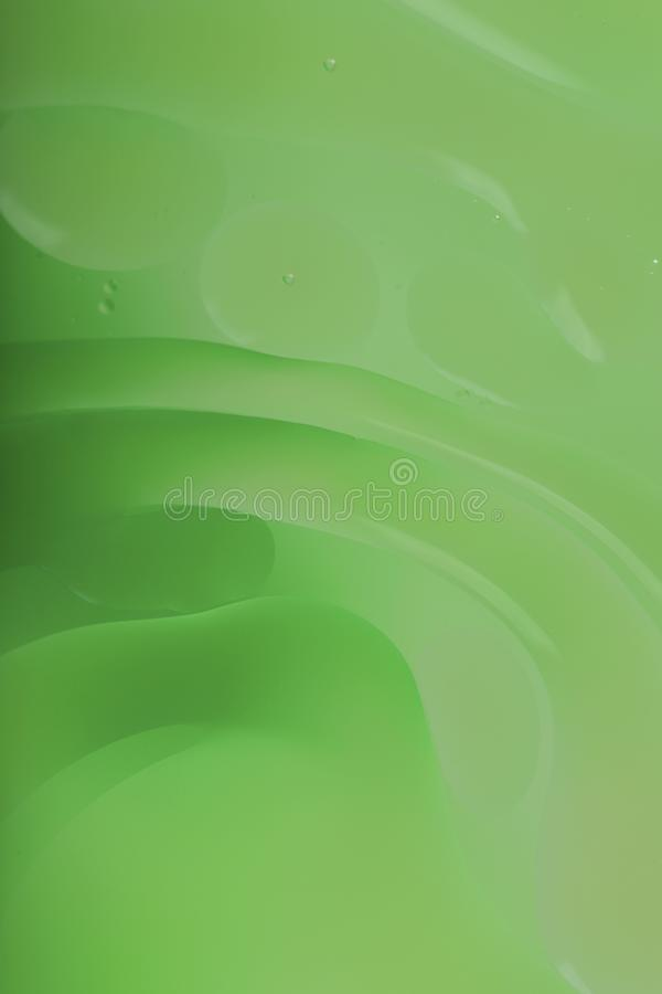 Blurred abstract background. Macro shot of oily liquid. Green circles and wavy lines of different sizes. stock illustration