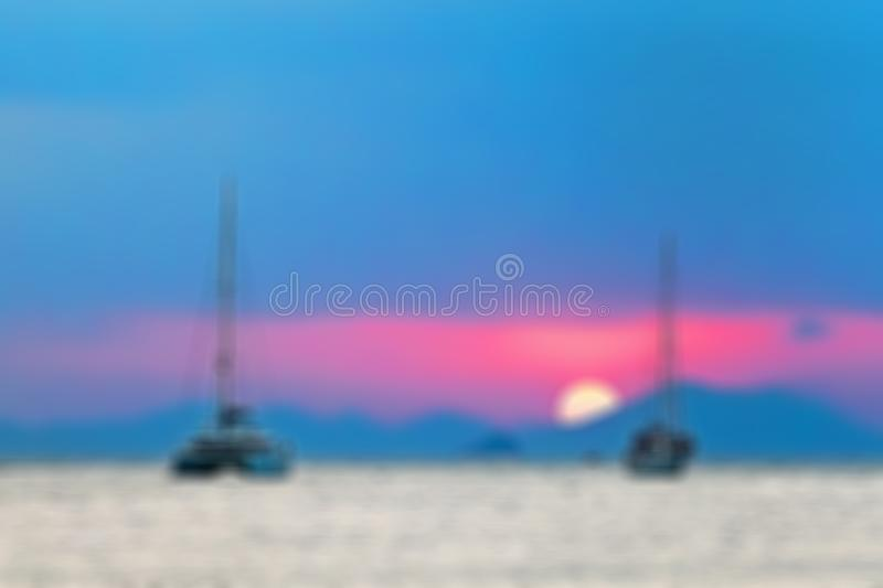 Blurred abstract background. Two sailing yachts in the sea. During sunset, the sun sets over the mountains.  royalty free stock photos
