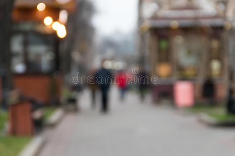 Blurred abstract background. Unrecognizable silhouettes of people walking on city street stock photography
