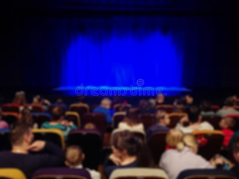Blurred abstract image. Auditorium of the theater. Parents with children before the show. Blue curtain on stage.  stock photo