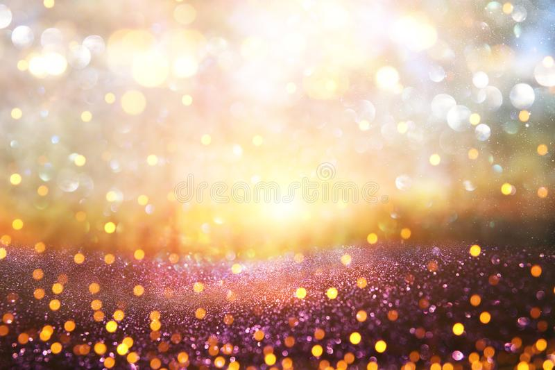 Blurred abstract photo of light burst among trees and glitter go. Lden bokeh lights royalty free stock photo