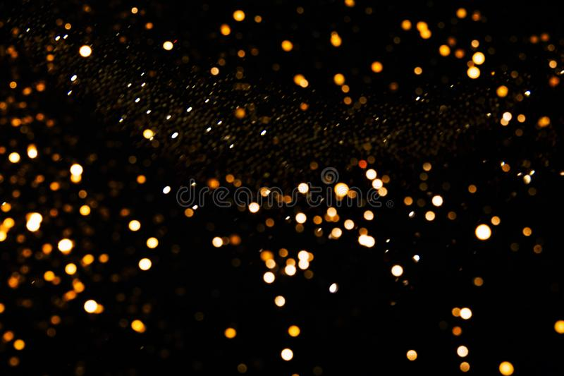 Blurred abstract silver and golden lights background on black backdrop. stock photography