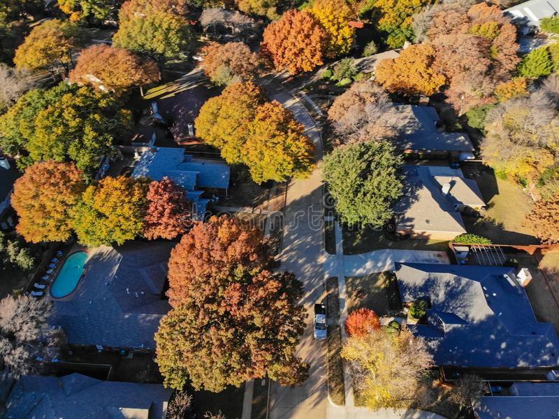 Blurry drone view residential houses with garden, garage and colorful leaves near Dallas. Blurred aerial view residential neighborhood with colorful fall foliage royalty free stock photo