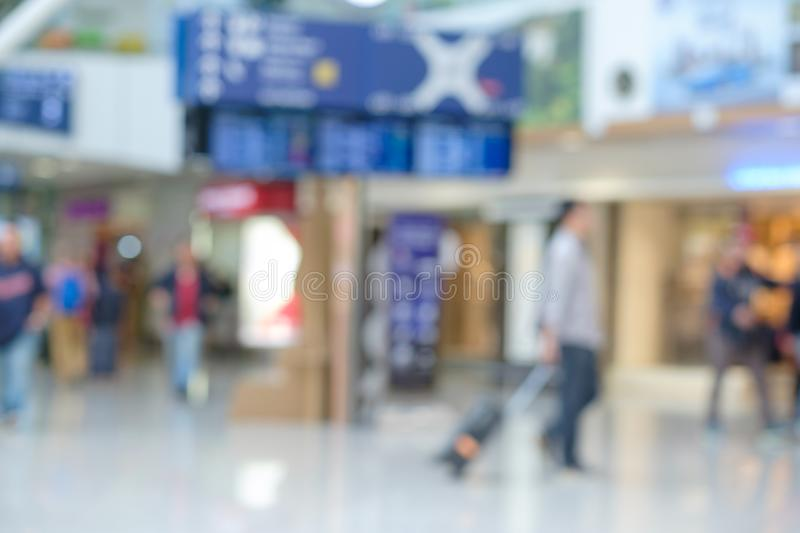 Blurred airport time table with passenger going with bag for travel at Malaysia international airport. Concept of travelling and vacation royalty free stock photo