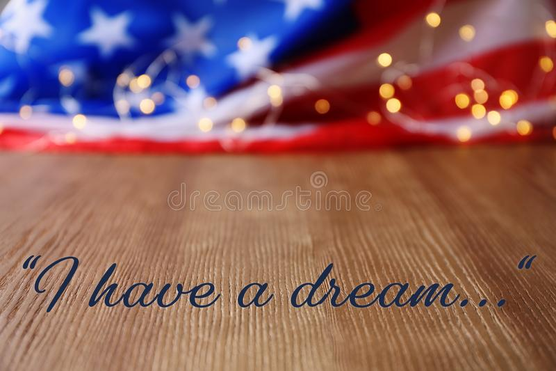 Blurred American flag and garland on wooden table. Space for text royalty free stock image