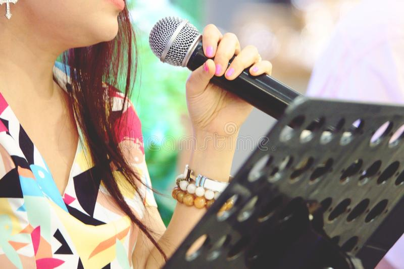 Blurred asia singer hands holding microphone  on stage stock images