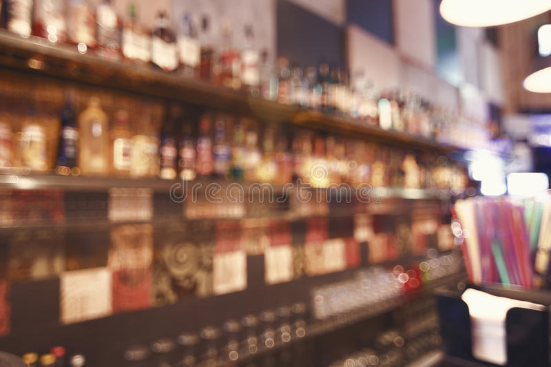 Blurred back bar. Bottles of spirits and liquor at the bar. Blurred desk in bar. royalty free stock photography