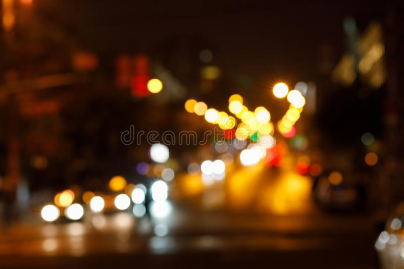 The blurred background of bright dipped headlamps with the illuminated night city landscape behind. royalty free stock photo