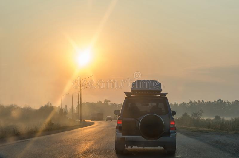 Car moving on the road in countryside early in the morning. View to the traffic with pillars and truck. Blurred background. Car moving on the road in stock photo