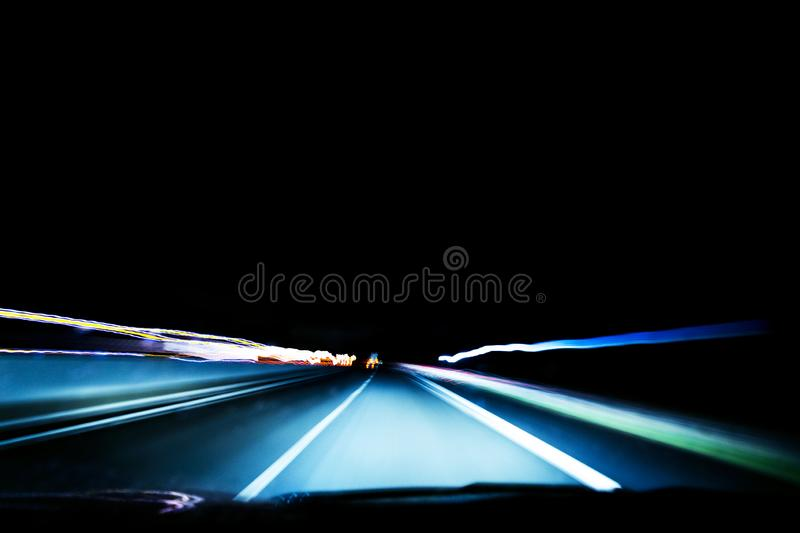 Blurred background with Cars light trails on a curved highway at night. Night traffic trails. Motion blur. Night road with traffic. Headlight motion. Cityscape royalty free stock photo