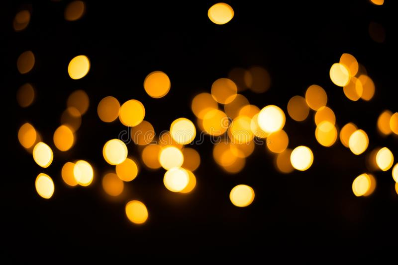 Blurred background. Christmas lights on a black background. Yellow light bulbs. Festive background stock photography