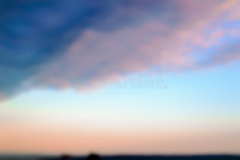 Blurred background of evening sky of pink and blue colors over a sea. Sunset sky pastel background royalty free stock photo